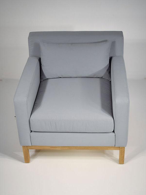 slim blue upholstered armchair with oak leg frame